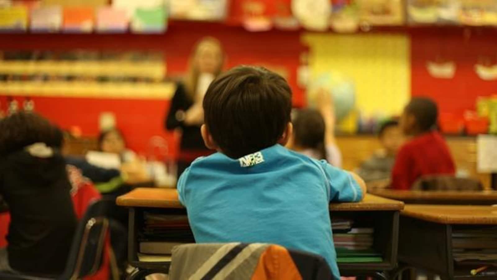 Un enfant assis de dos dans une salle de classe.