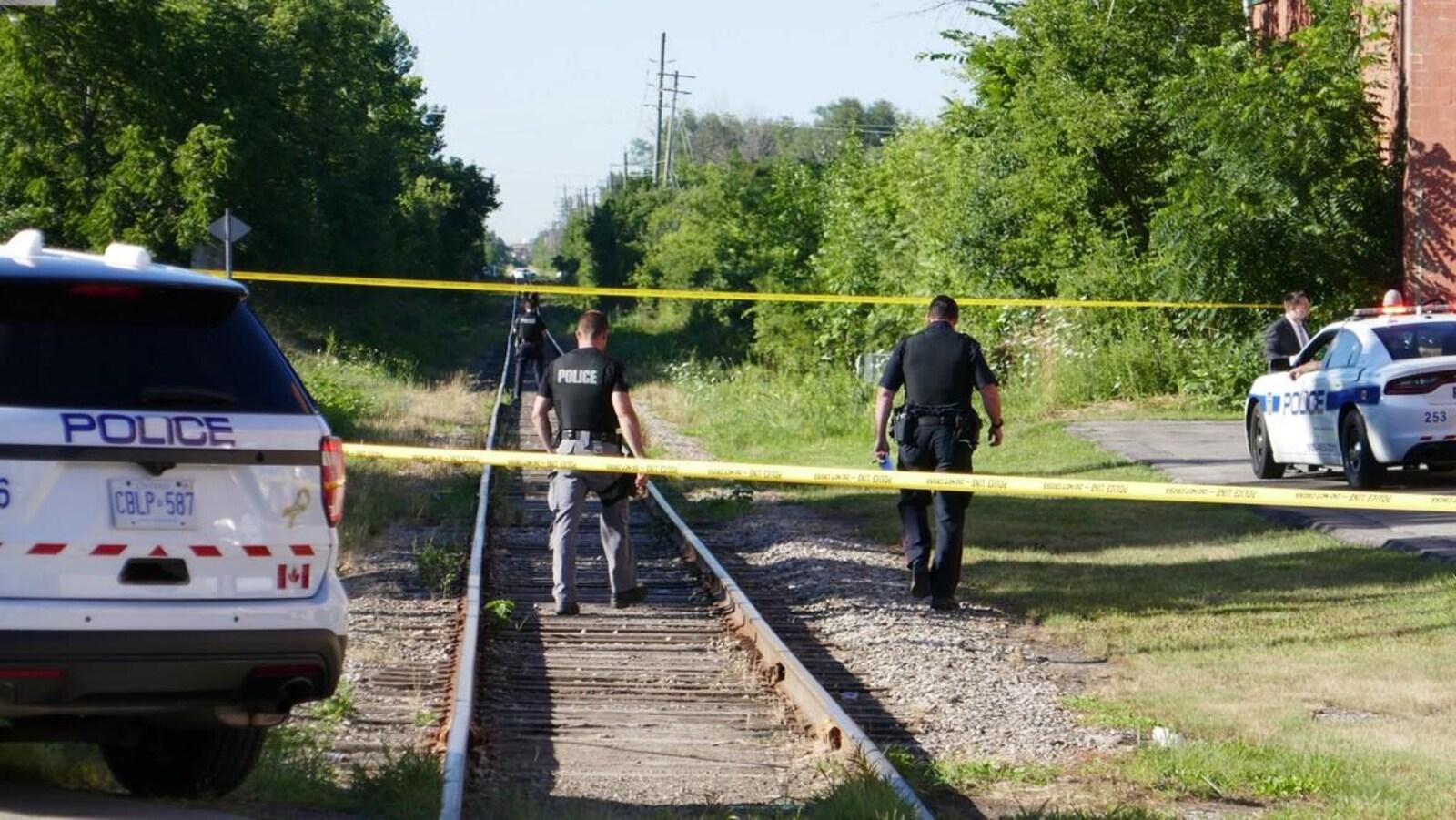 Photo de policiers qui marchent sur une voie ferrée derrière une banderole de police.