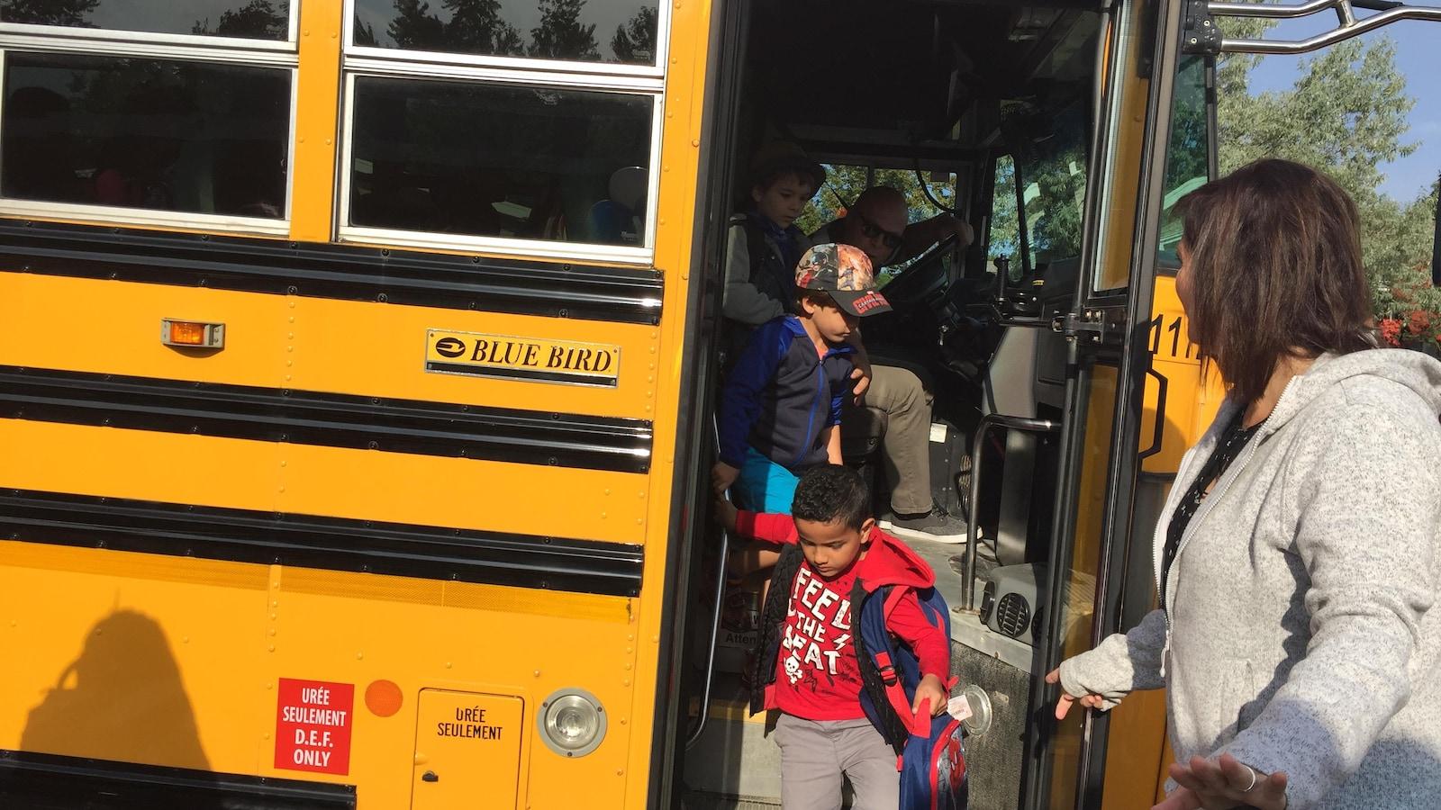 Des enfants descendent d'un autobus scolaire.