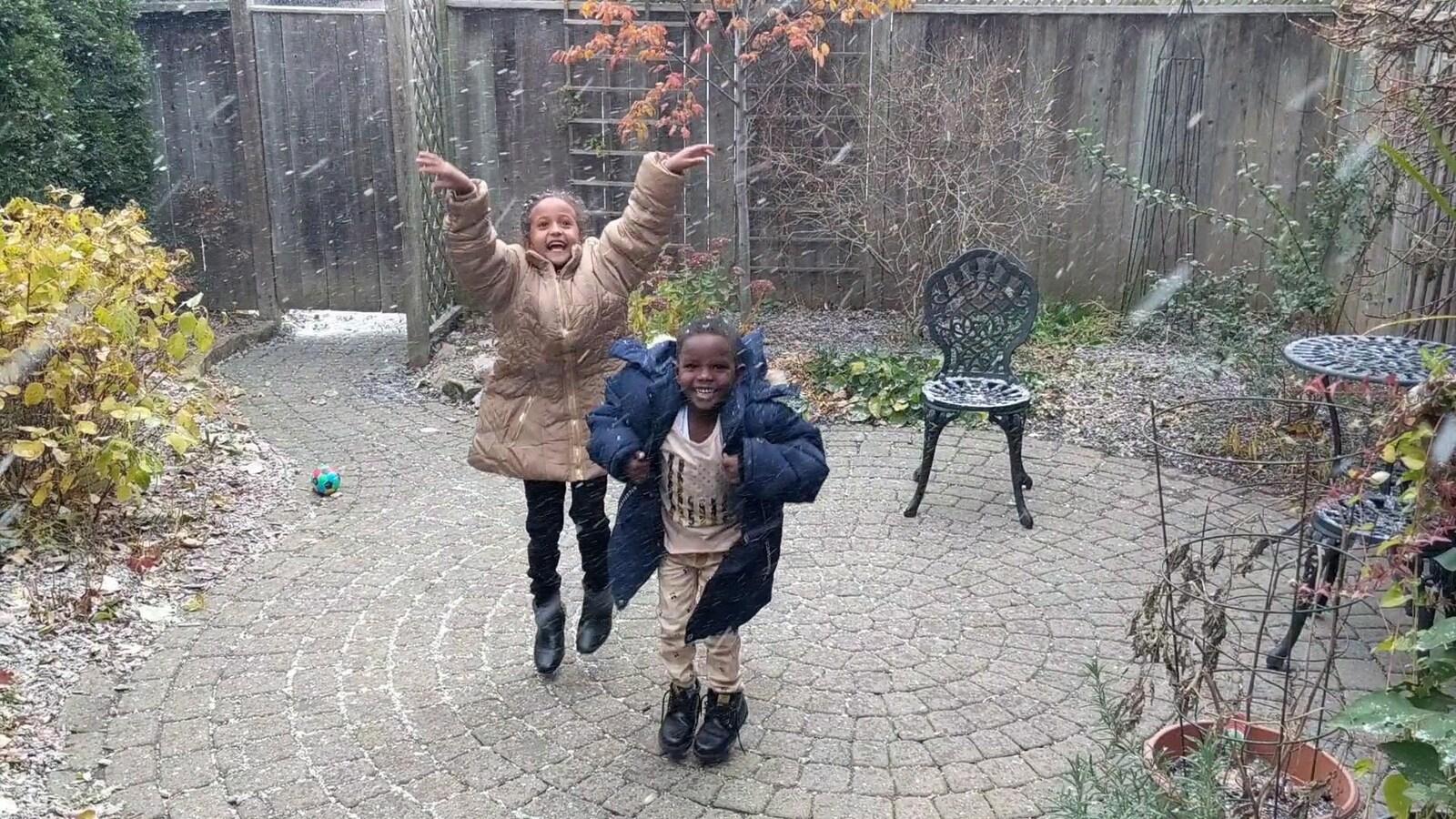 Deux jeunes enfants qui dansent dans la neige.