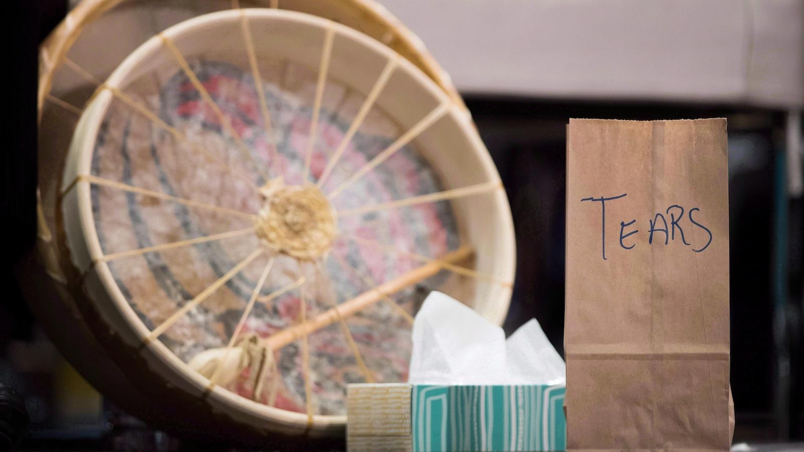 Un sac de papier brun sur lequel est écrit «larmes» repose à côté d'une boîte de papiers-mouchoirs et de deux tambours rituels autochtones en peau d'animal.