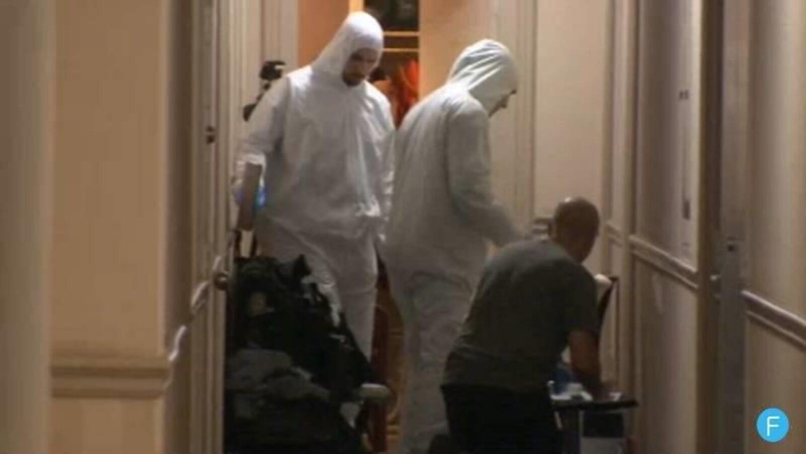Des policiers près de la porte d'entrée d'un appartement