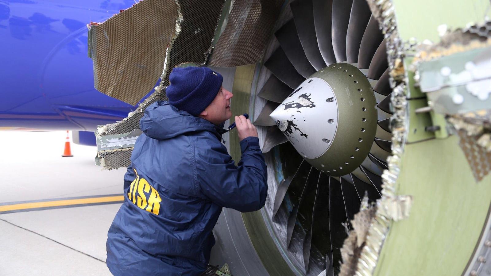 Un enquêteur du Bureau américain de la sécurité des transports examine le moteur endommagé de l'avion de Southwest Airlines qui a atterri d'urgence à Philadelphie le 17 avril 2018.