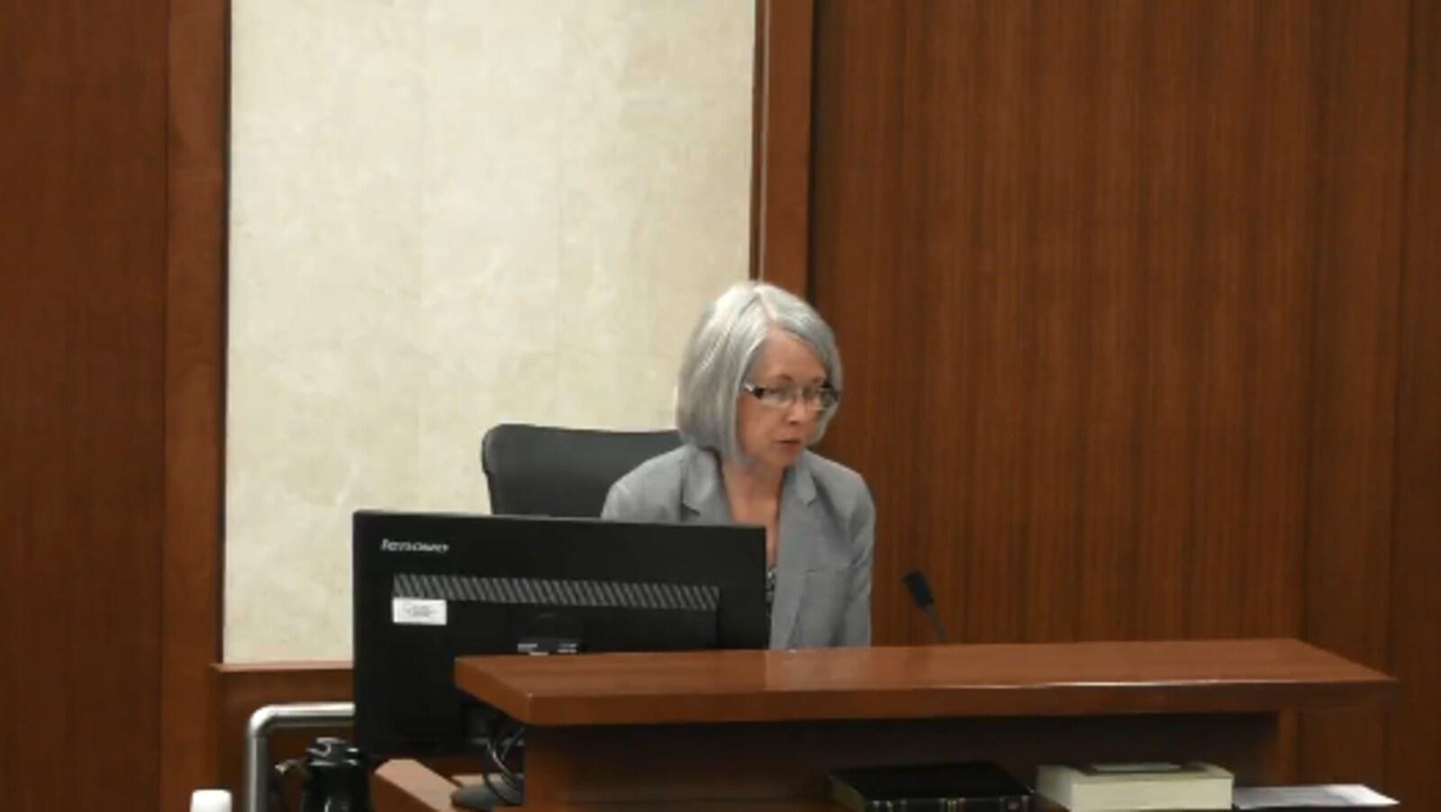 Une femme témoigne dans une salle de cour.