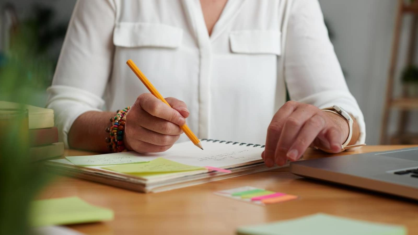 Une femme écrit des notes dans un cahier, un crayon à la main.