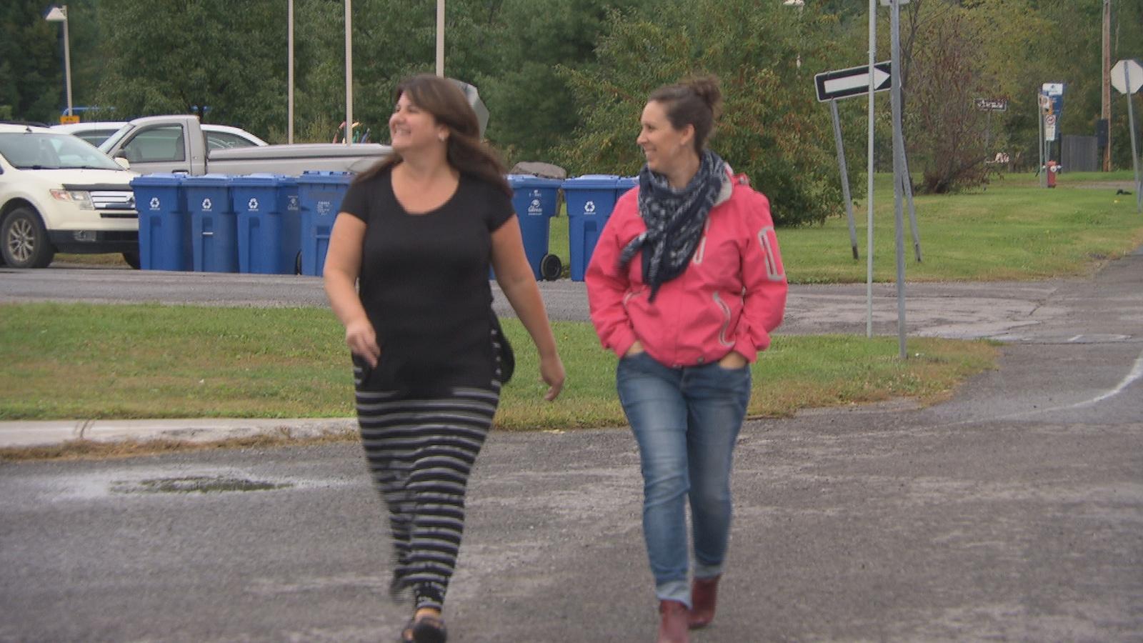 Severine Wiels et Geneviève Deschênes marchent devant une école.