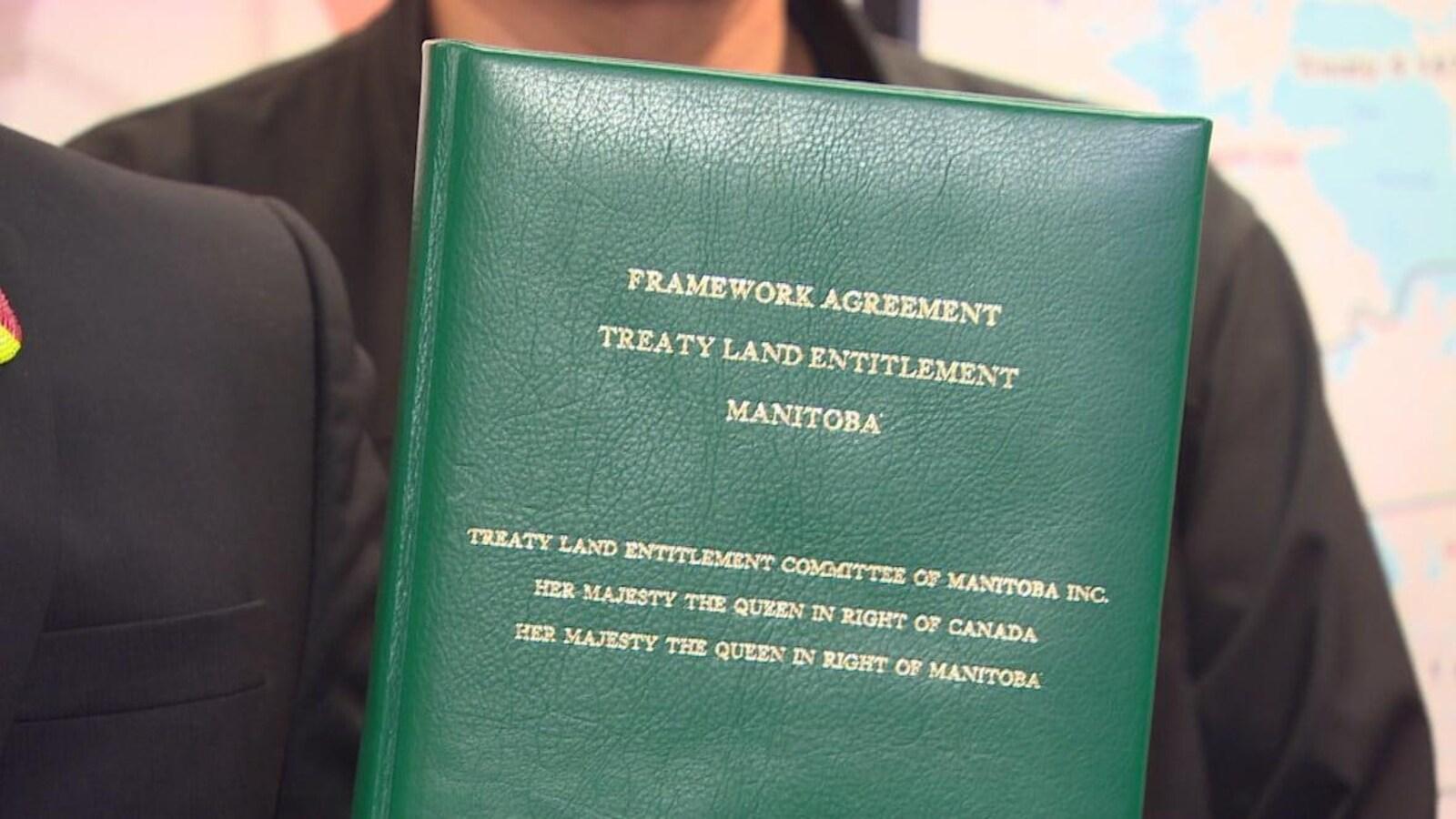 Une personne qu'on ne voit pas, tient un document relié en vert sur lequel on peut lire le titre de l'entente.