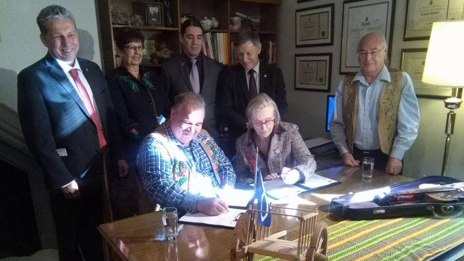 Le président de la Fédération des Métis du Manitoba, David Chartrand, et la ministre  des Affaires autochtones et du Nord, Carolyn Bennett, signent un accord à Ottawa.