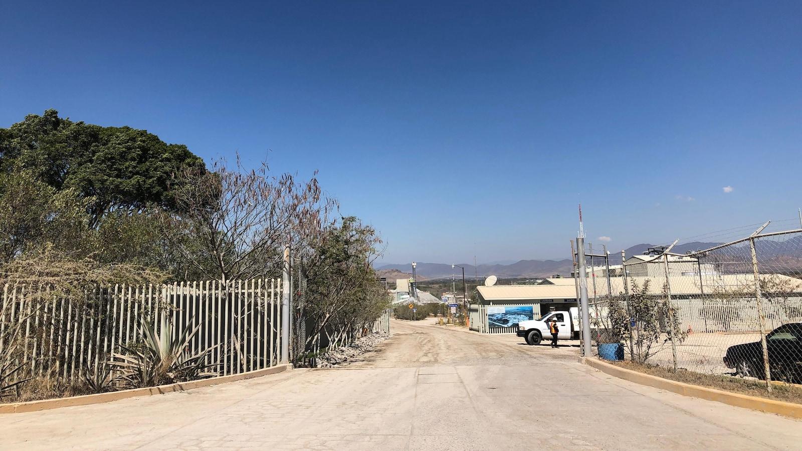 À l'entrée, un travailleur près d'une camionnette blanche, et plus loin, des bâtiments.