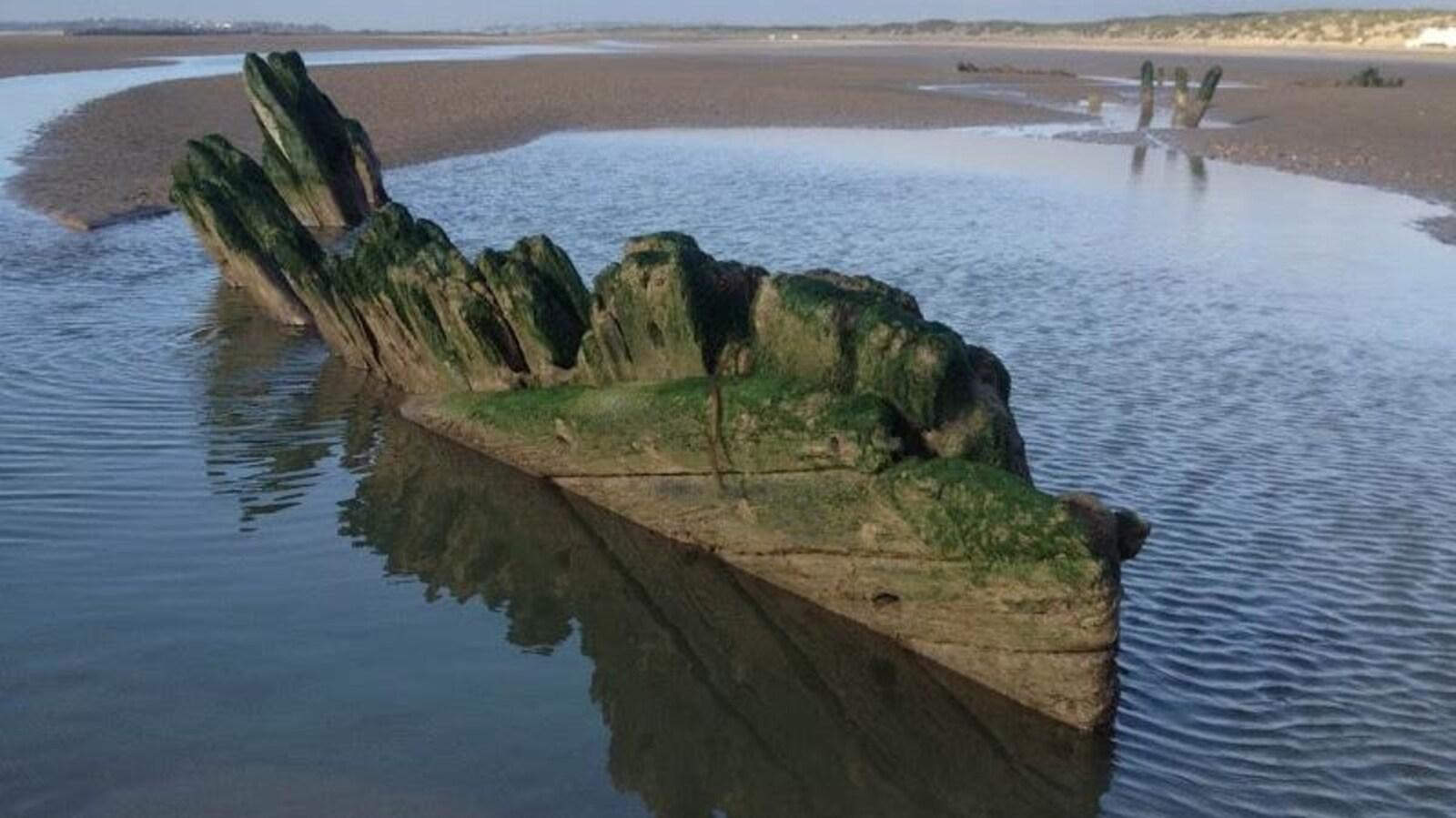 Une partie de la coque en bois sortant du sable