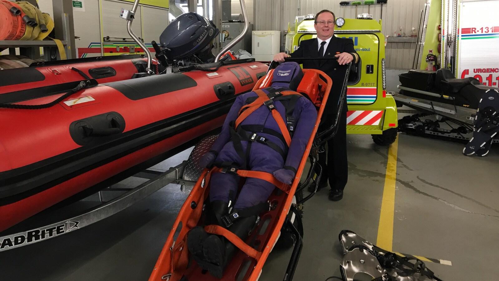 Un homme tient une civière près d'un nouveau canot pneumatique pour des interventions en zones isolées.