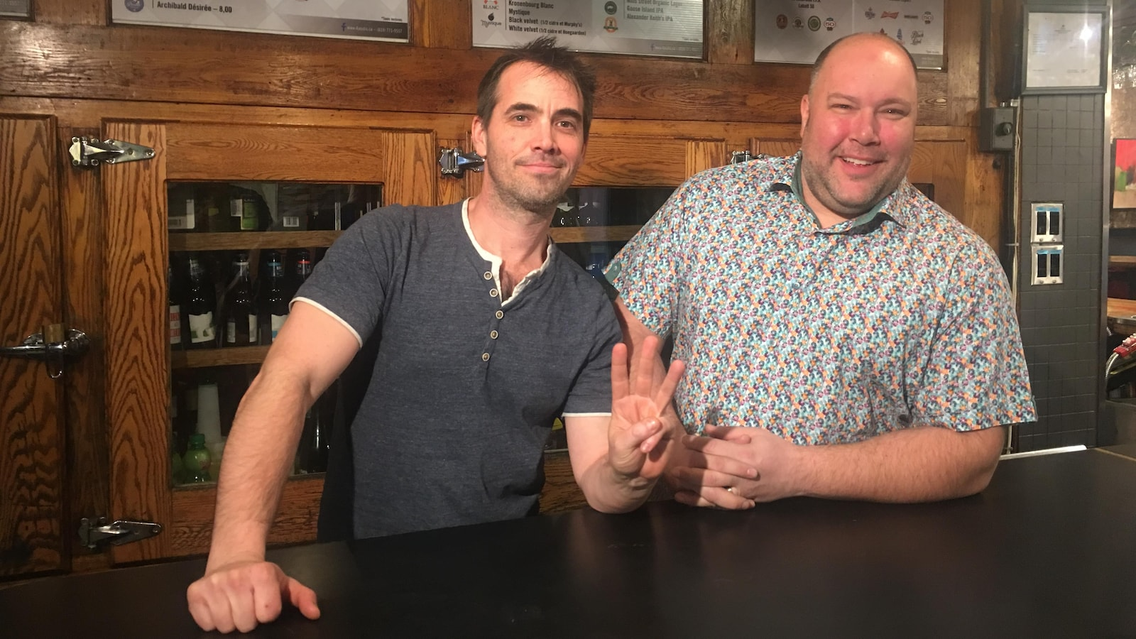 Derrière un bar, Éric Gaudreault lève trois doigts de sa main gauche, pendant qu'Alexandre Leblanc sourit.