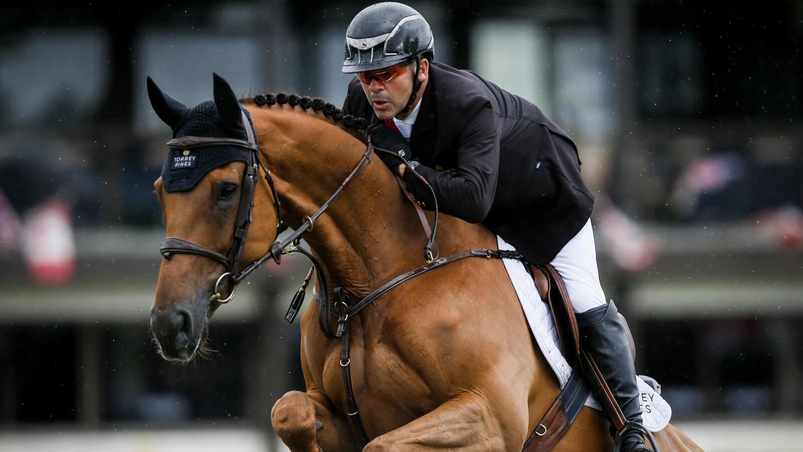 Éric Lamaze est sur son cheval, Chacco Kid, lors d'une épreuve de saut d'obstacles.