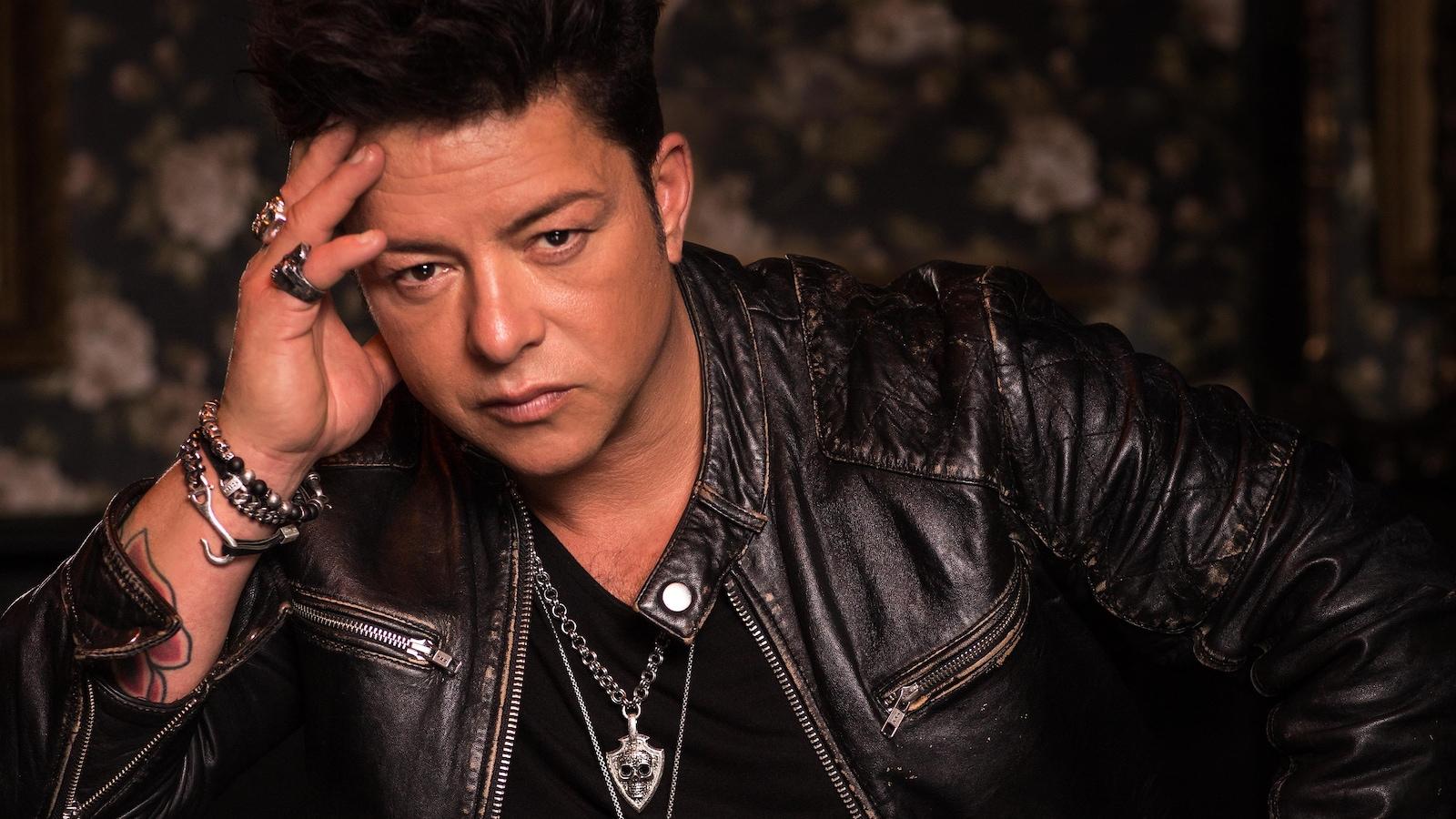 Le chanteur prend la pose dans son éternel veston de cuir, les bagues aux doigts.
