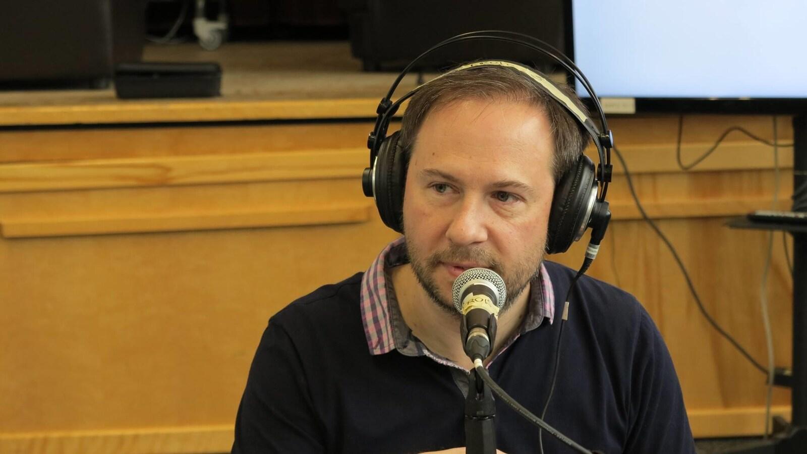 Éric dans un studio de radio avec des écouteurs sur les oreilles.