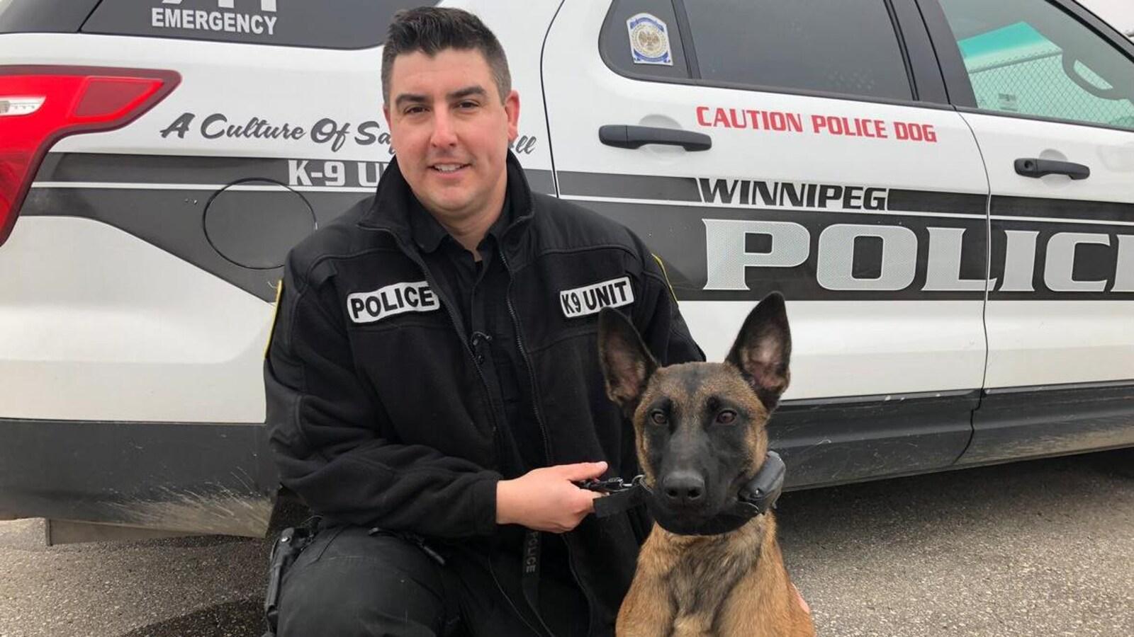 Un policier tient un chien en laisse devant une voiture de police.