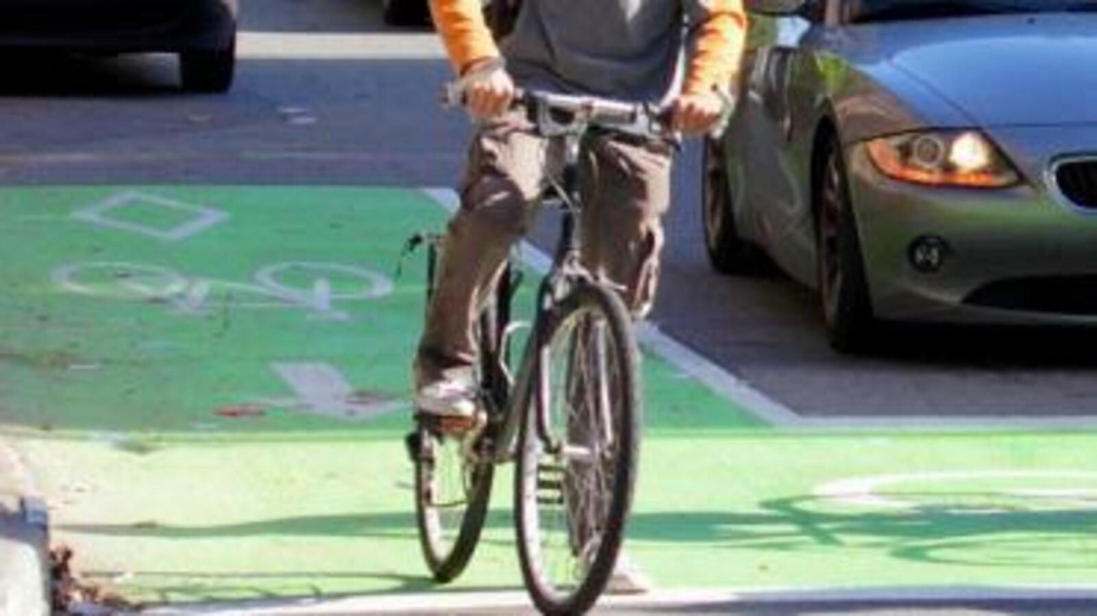Sas de vélo à Montréal, un espace marqué en vert où l'on voit un cycliste arrêté, avec derrière lui une voiture arrêtée à une intersection.