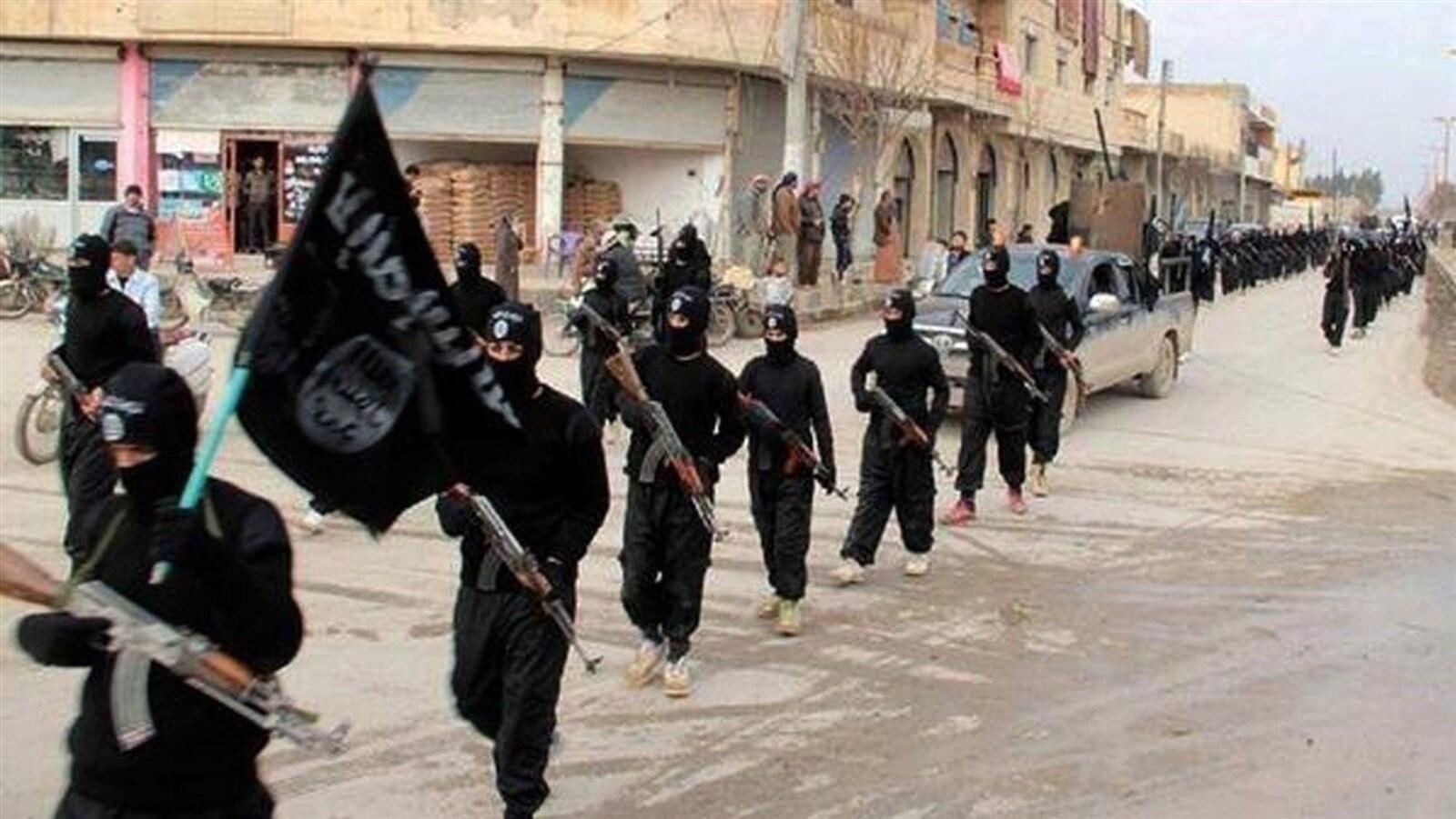 Des soldats armés et vêtus de noir défilent dans une rue avec un drapeau noir.