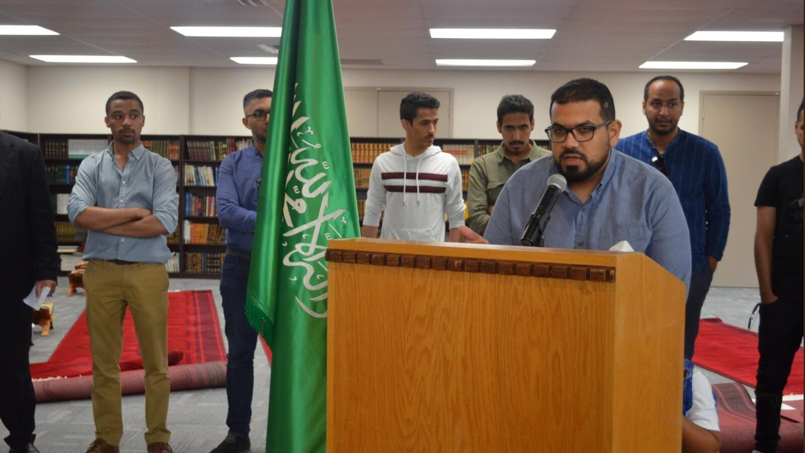 Un homme portant des lunettes parle au micro devant un pupitre. Derrière lui, plusieurs hommes sont debout derrière le drapeau saoudien.