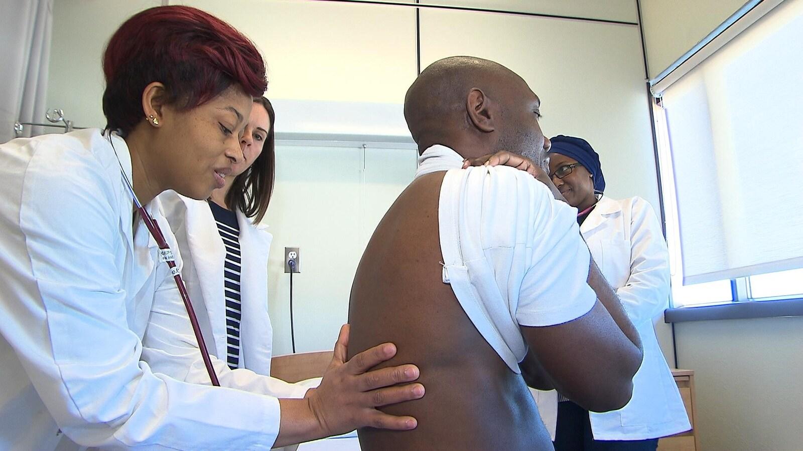 Elle ausculte le dos d'un patient.