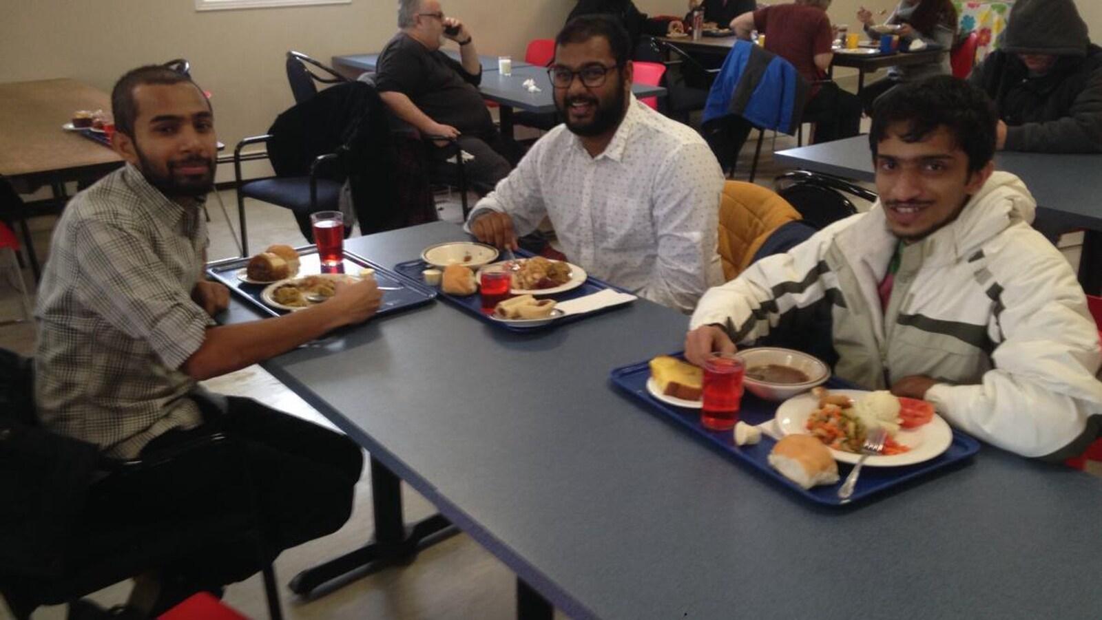 Trois étudiants posés devant leur repas dans une soupe populaire.