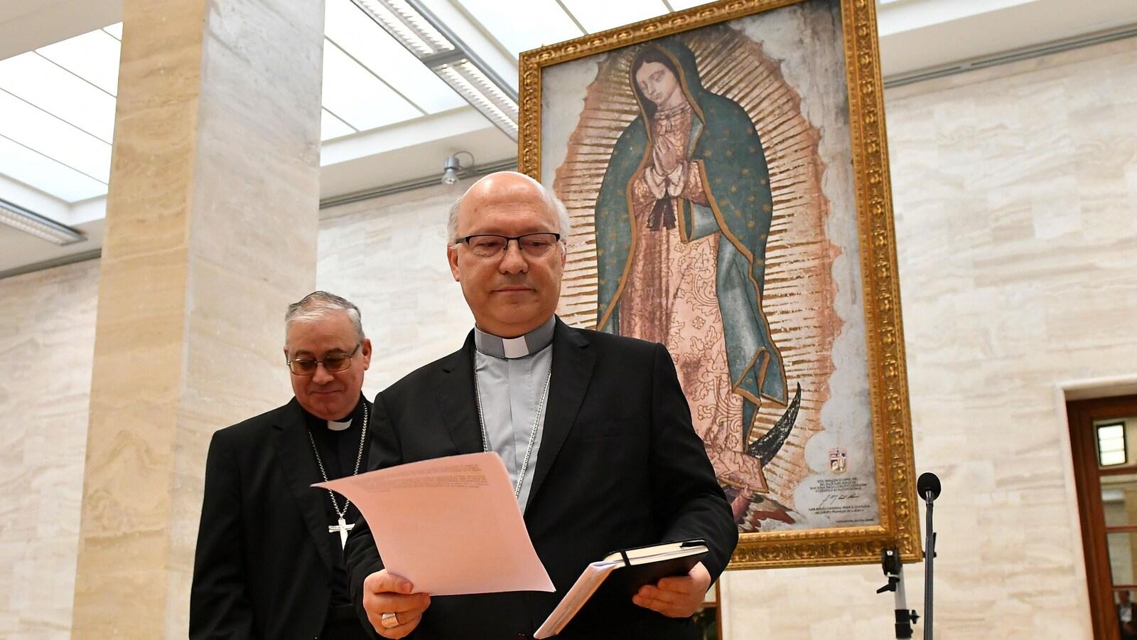 Les deux membres de la conférence épiscopale chilienne arrivent pour leur conférence de presse, donné devant une image religieuse.