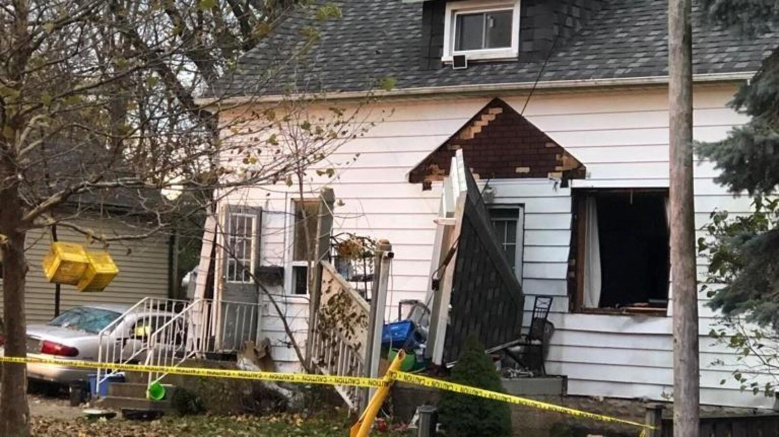 Photo d'une maison blanche dont un mur et une portion du portique ont été soufflés par une explosion.