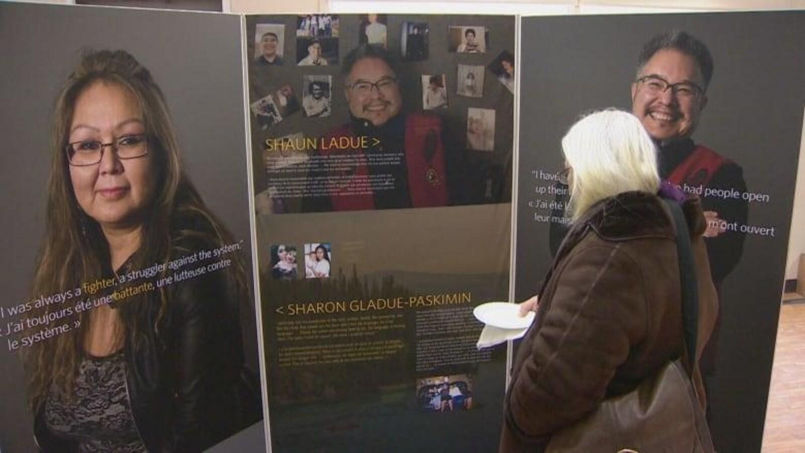 Une femme regarde les panneaux de l'exposition.