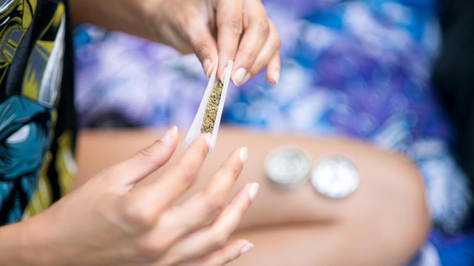 Gros plan sur les mains d'une femme roulant un joint de cannabis.