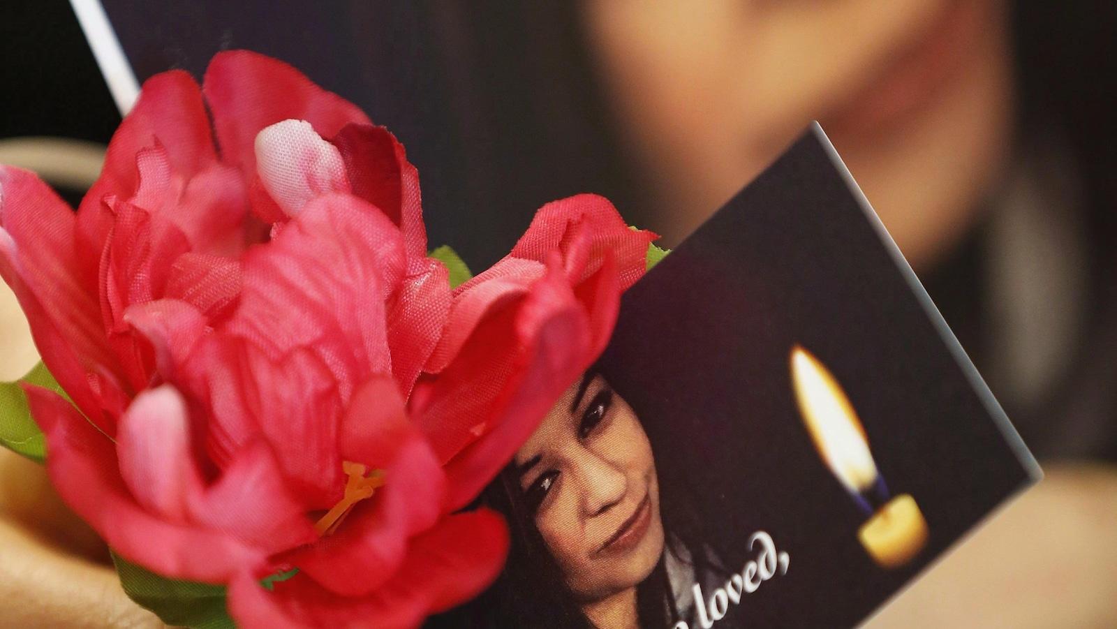 Une femme tient des fleurs et une photo représentant Christine Wood, une jeune femme autochtone de Winnipeg portée disparue au printemps 2016. Les restes de Mme Wood ont été retrouvés près d'un an plus tard, dans un champ de la région.
