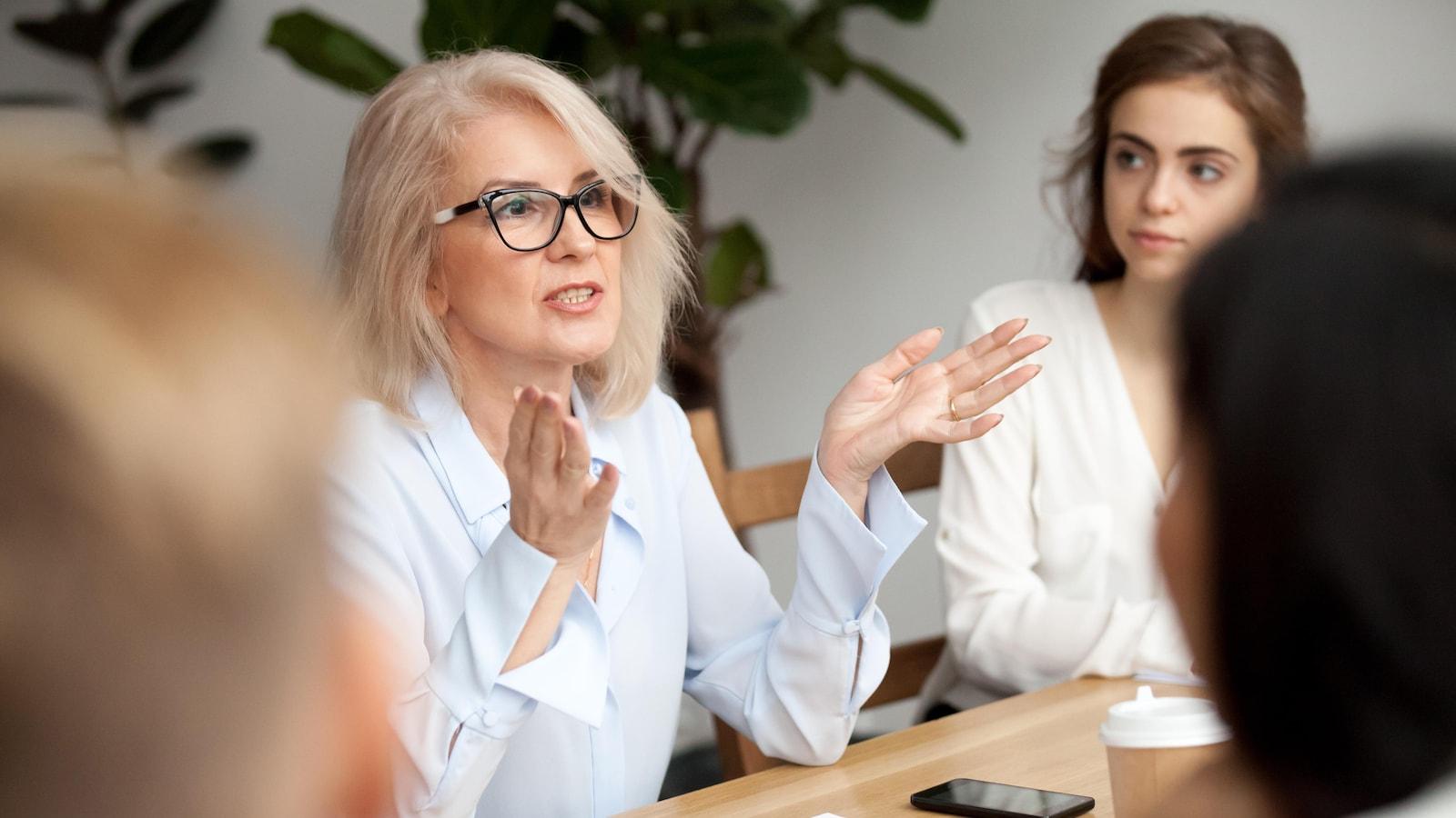 Une femme parle à plusieurs personnes réunies autour d'une table.