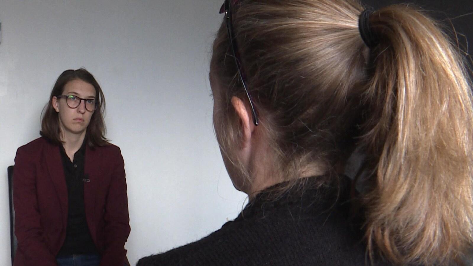 Deux femmes assises se font face; l'une d'elle est vue de dos.