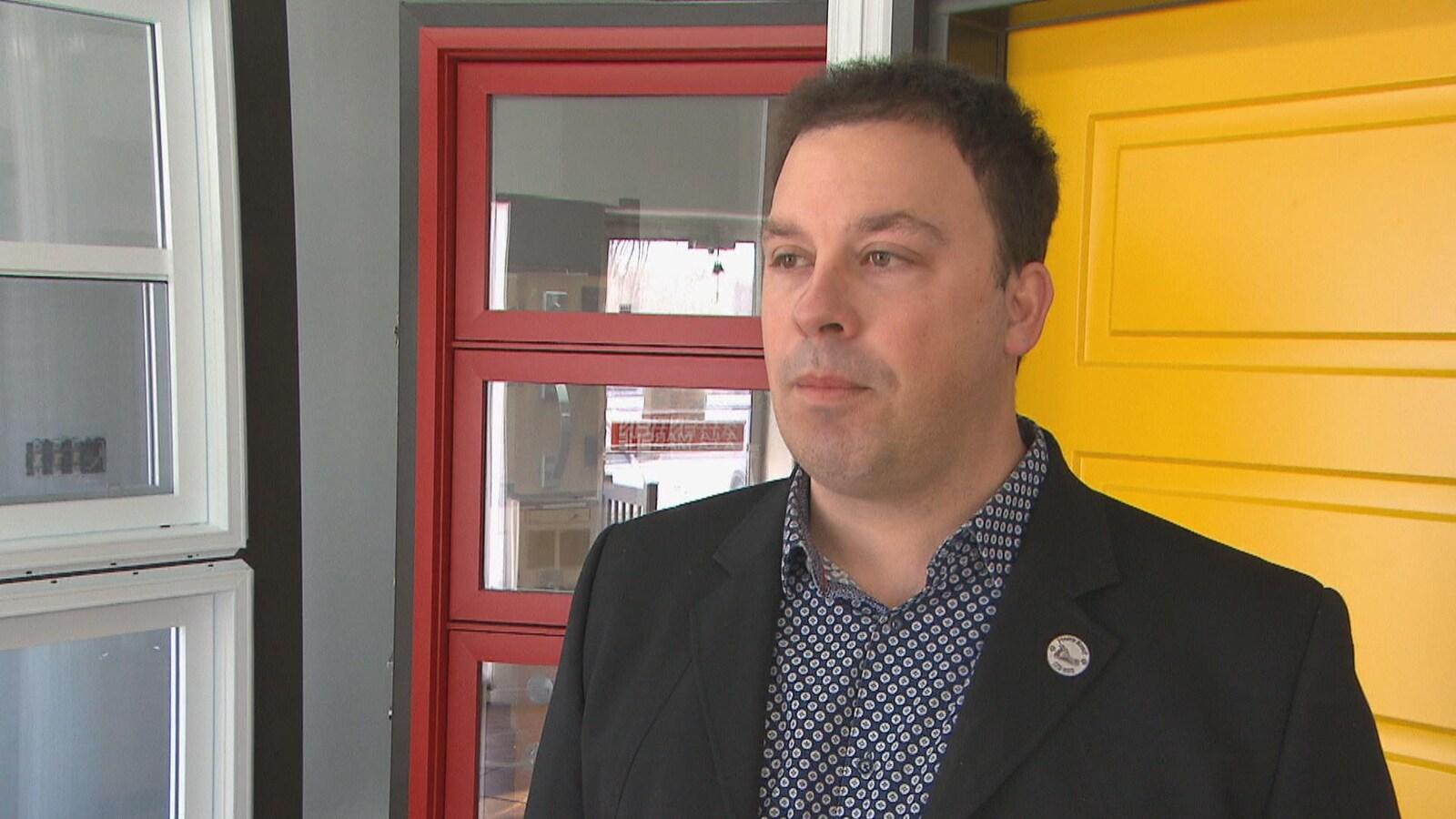 Philippe Lebel en entrevue devant des portes et fenêtres.