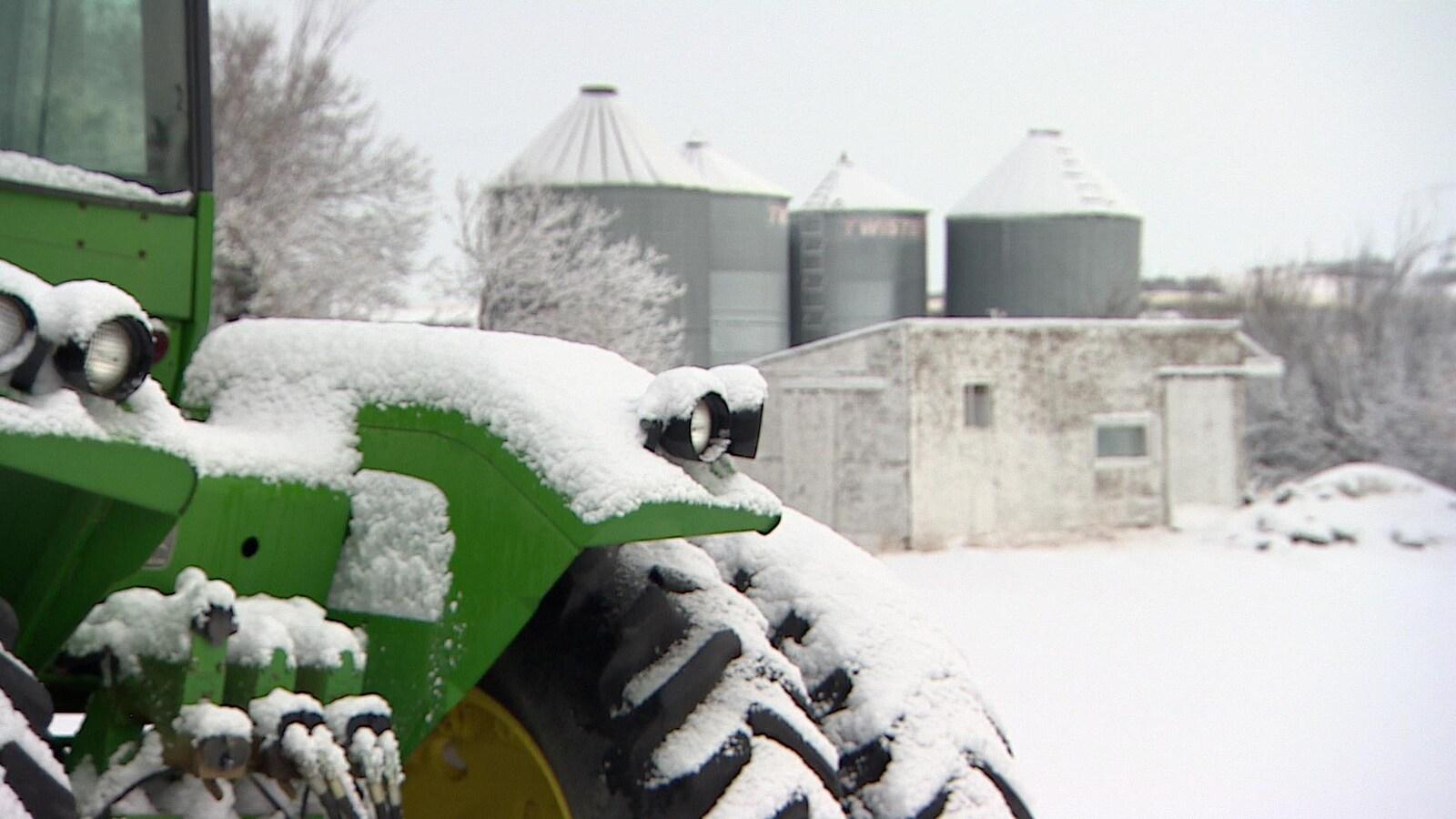 Un tracteur vert enneigé devant un cabanon et des installations agricoles, en temps de neige.
