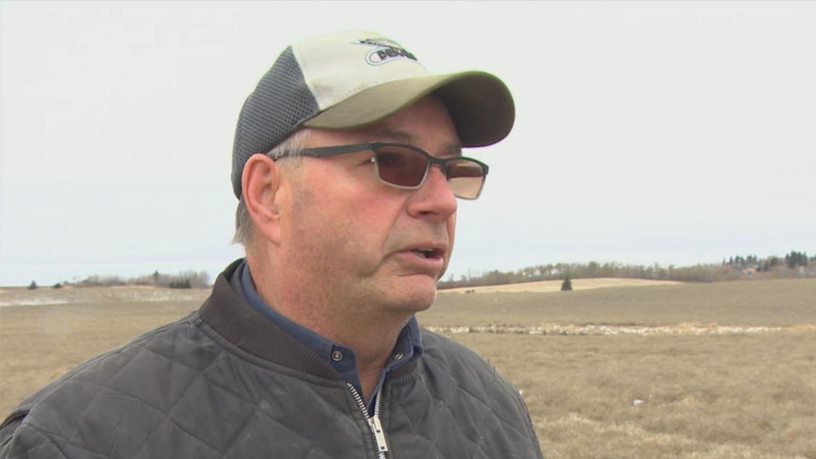 Un homme aux cheveux grisonnant avec une casquette et des lunettes se tient dans un champ sous un ciel gris.