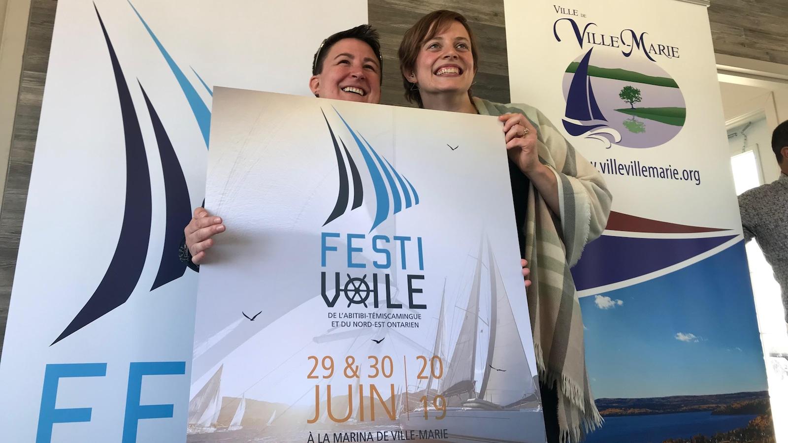 Deux femmes sourient en tenant une affiche du Festivoile de l'Abitibi-Témiscamingue et du Nord-Est ontarien.