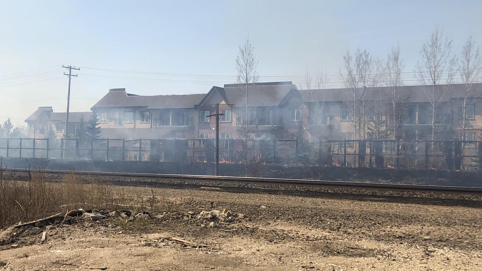 De la fumée s'échappe d'un feu de broussailles entre des rails et une clôture derrière laquelle se trouvent des résidences