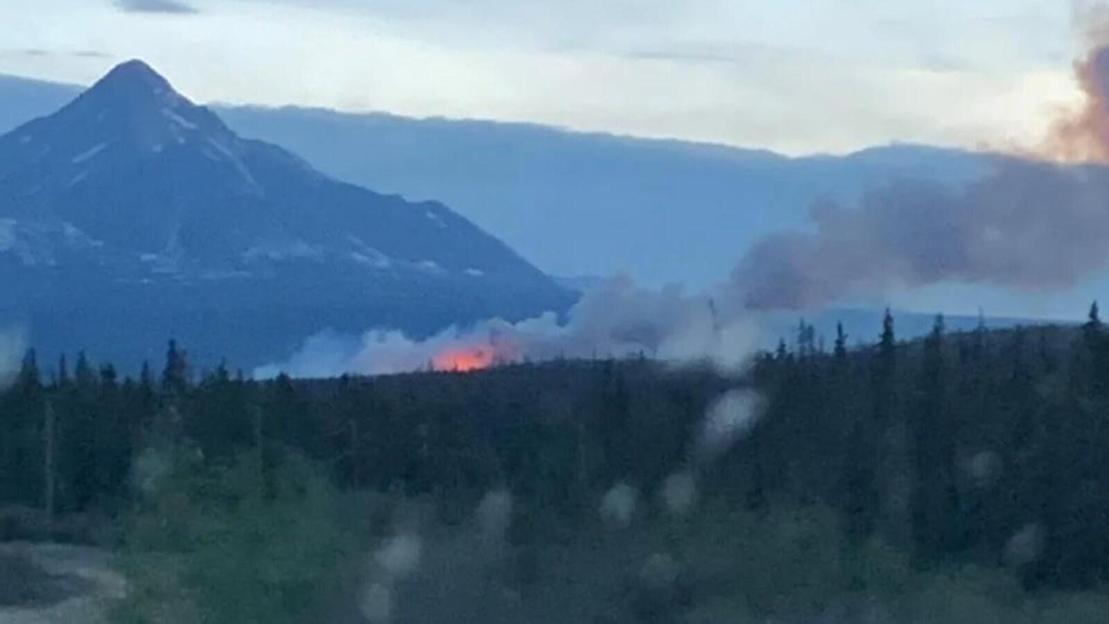 Des flammes visible de loin au pied d'une montagne