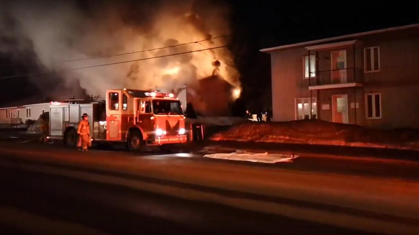 Des camions de pompiers devant une maison en feu