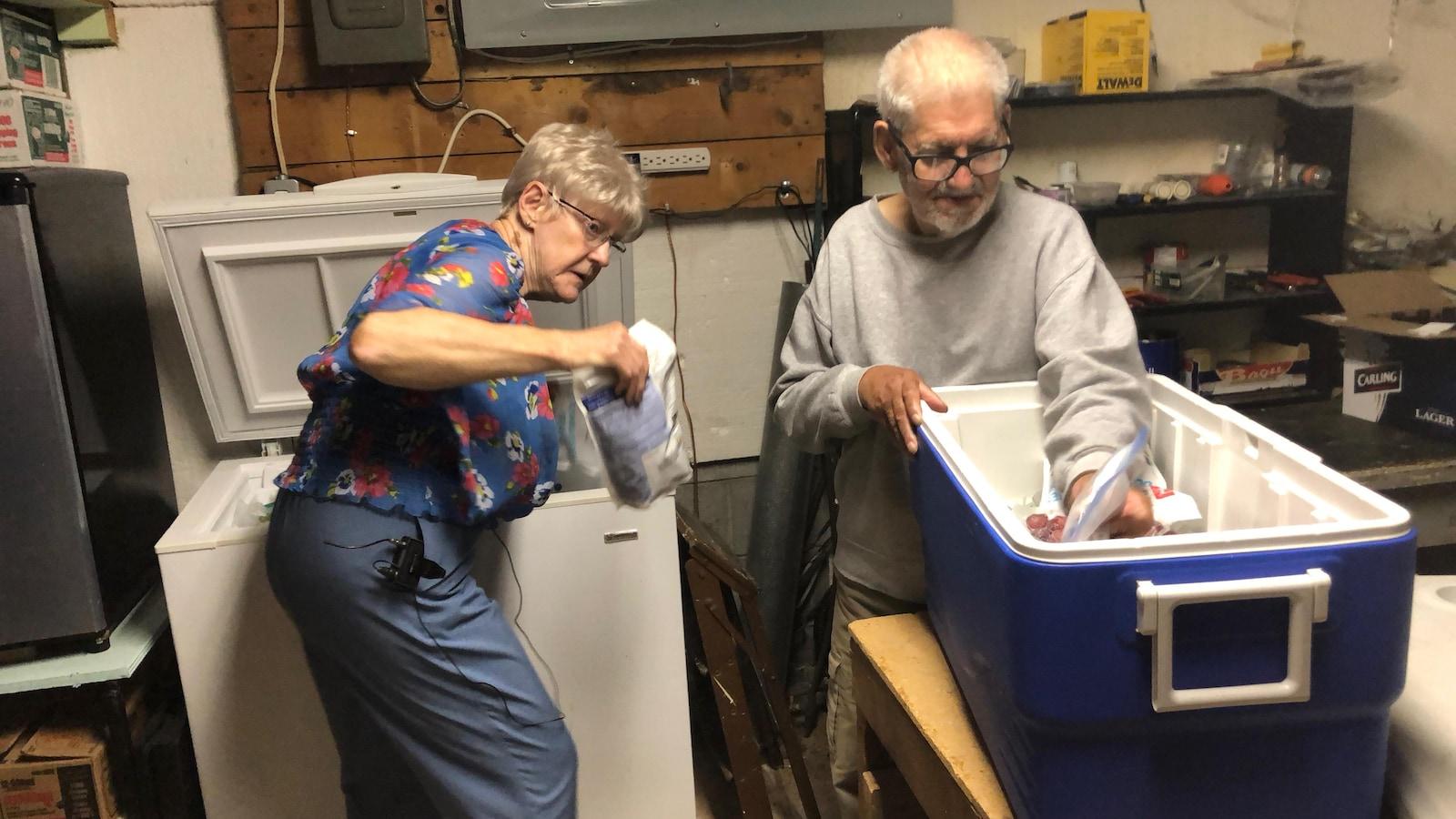La femme sort un paquet de son congélateur pour le mettre dans une grosse glacière avec l'aide de son conjoint.