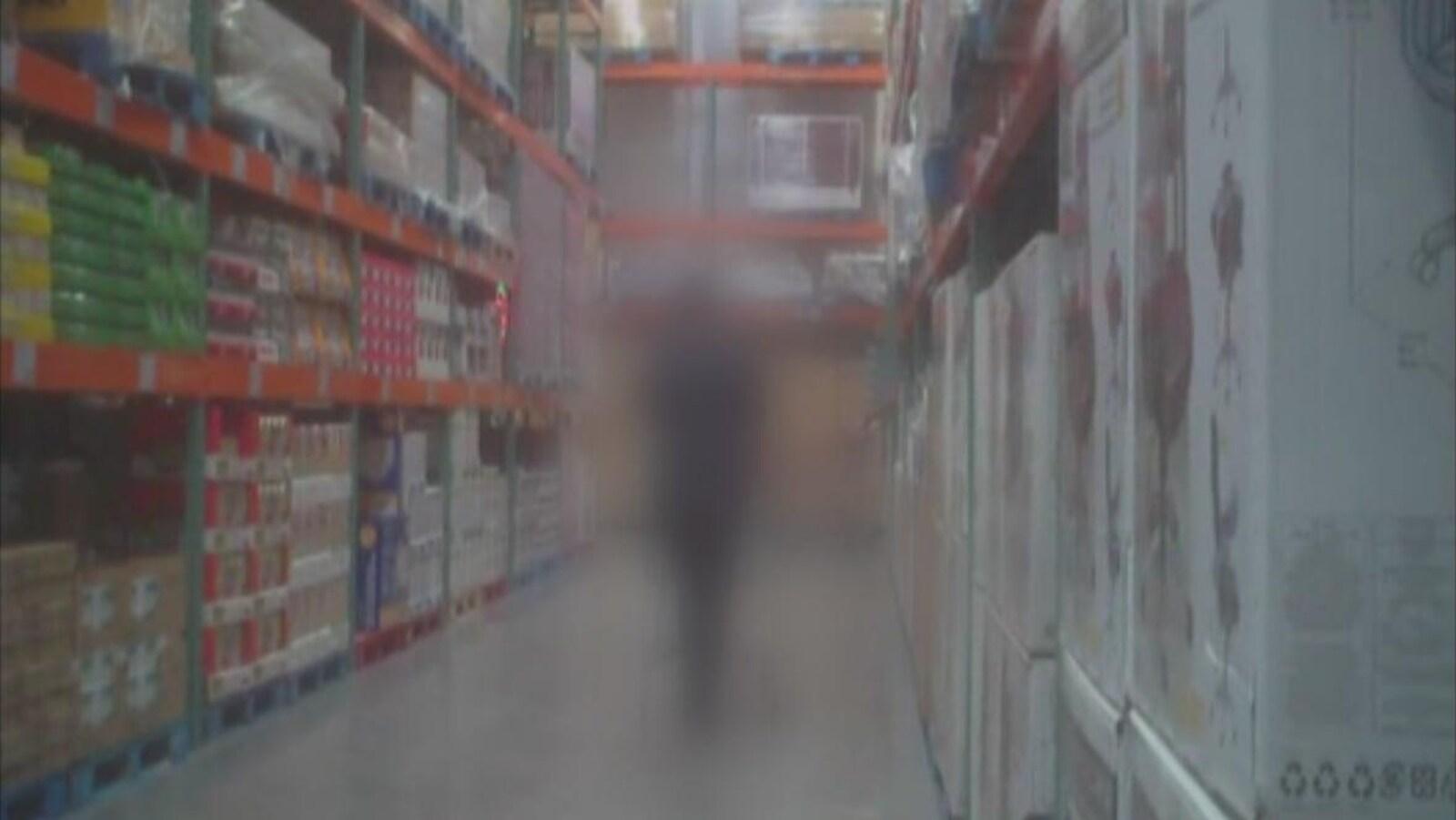 Une silhouette brouillée dans l'allée d'un magasin à grande surface.
