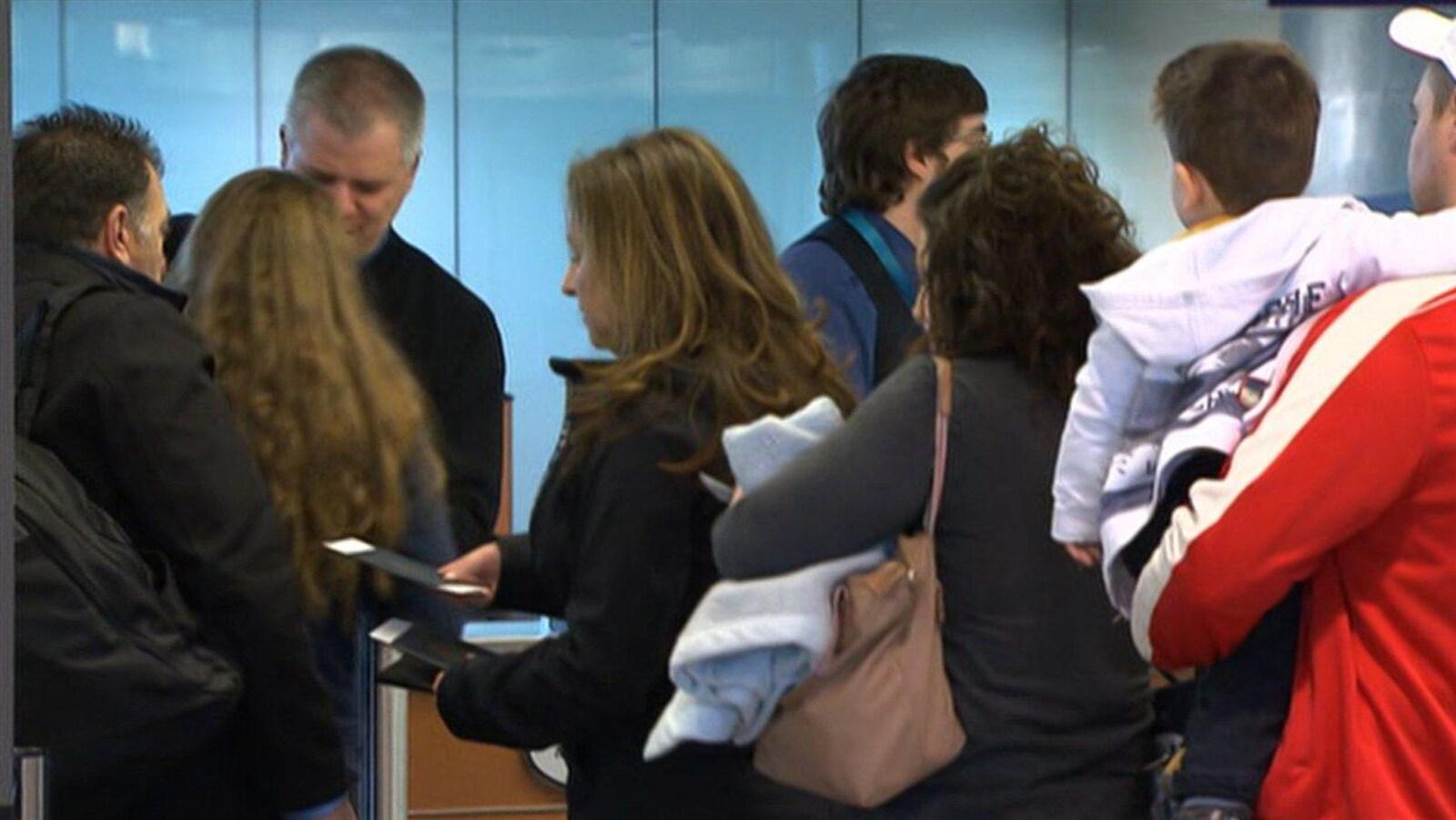 Des gens font la file à l'Aéroport international Pierre-Elliott-Trudeau de Montréal.