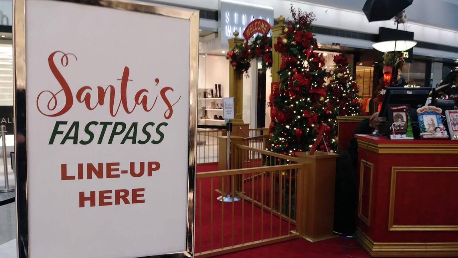 L'entrée du village du père Noël d'un centre commercial arbore une affiche indiquant, en anglais, l'entrée de la file d'attente rapide Santa's FastPass.