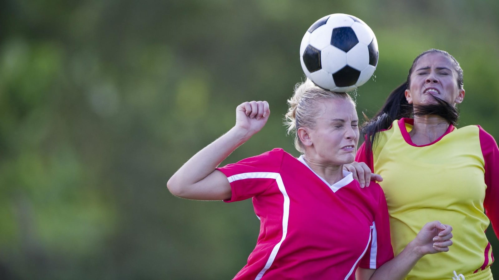 Une jeune femme frappe un ballon de soccer avec la tête.