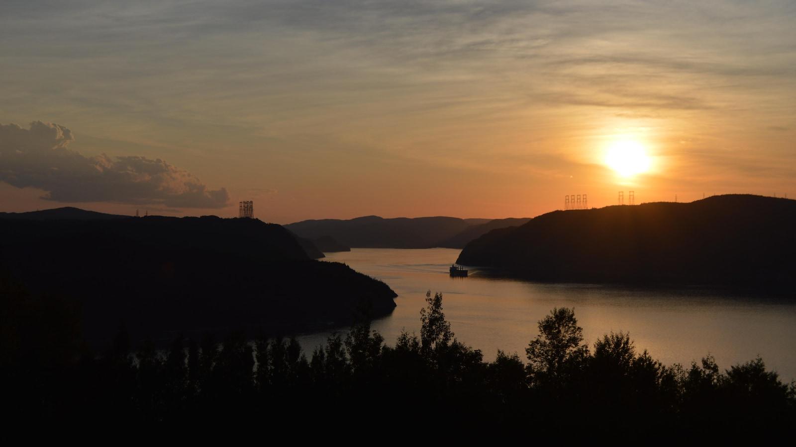 On voit le soleil se coucher sur les caps bordant la rivière Saguenay.