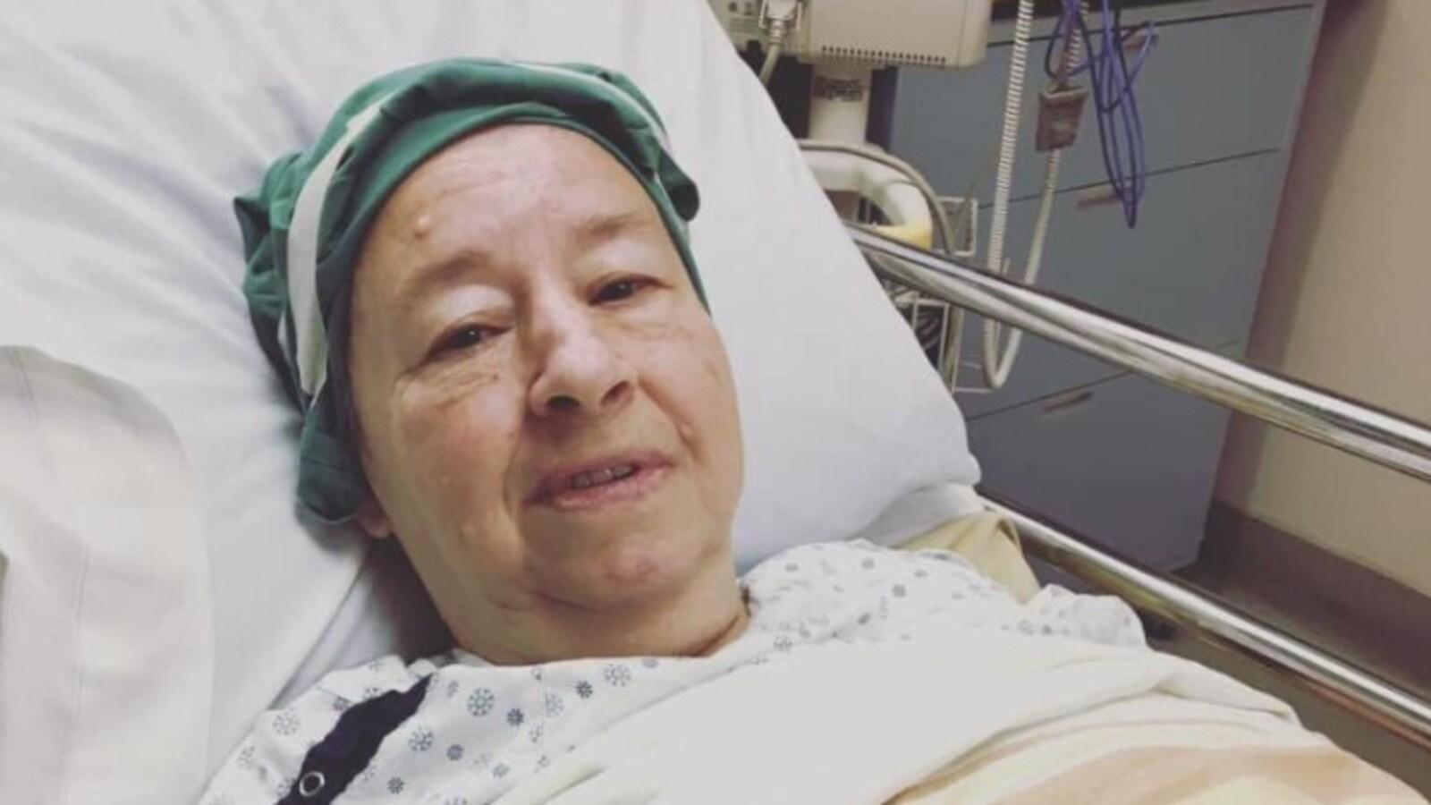 Une femme couchée dans un lit d'hôpital, l'air malade.