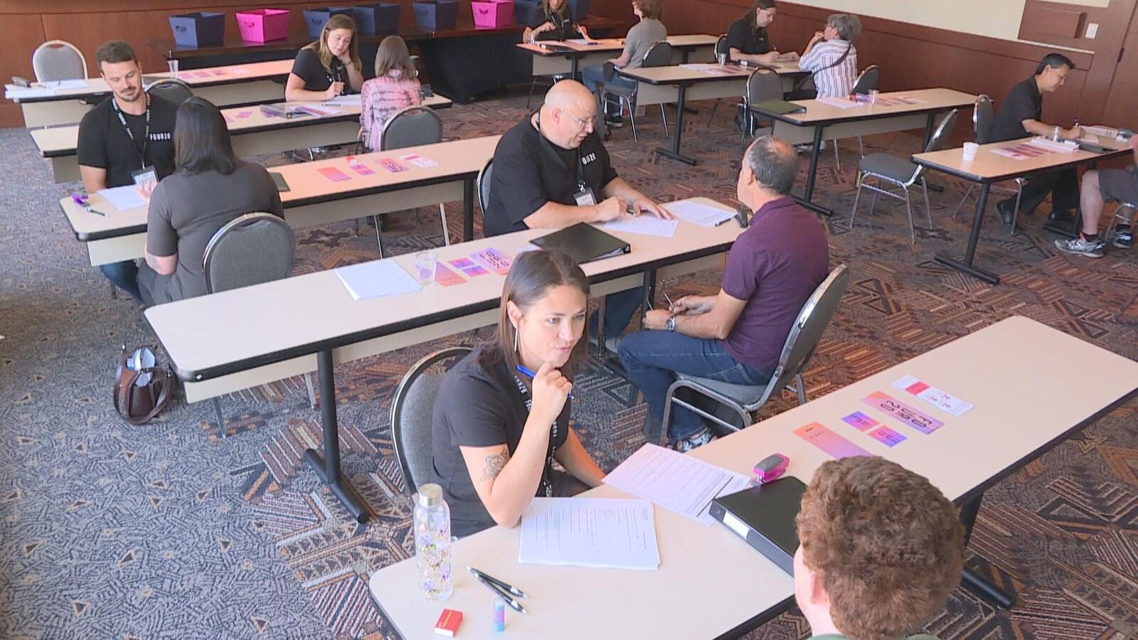 Vue sur quelques tables dans une grande salle. À chacune des tables, il y a deux personnes qui discutent ensemble. Il y a des papiers sur les tables.