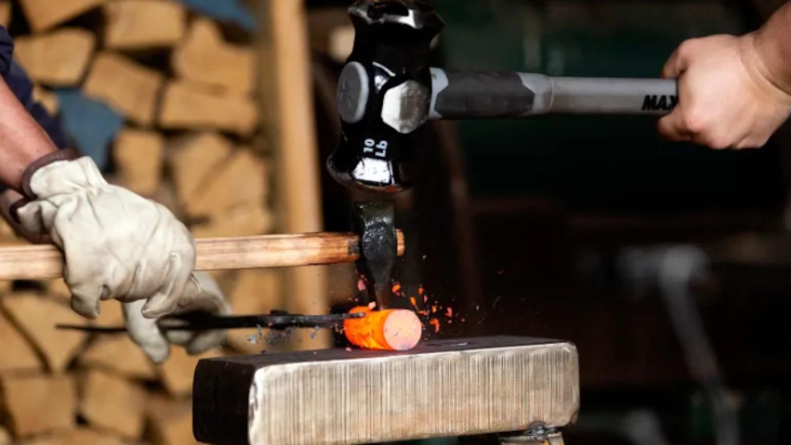 Deux marteaux frappent une pièce de fer sorti du four.