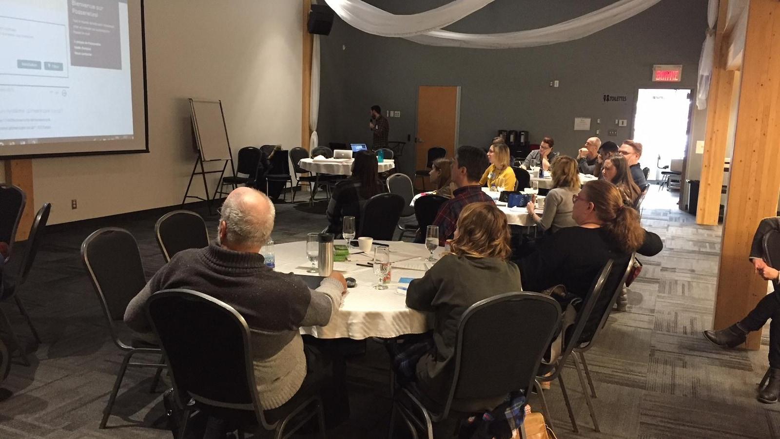 Des gens réunis lors d'un congrès regardent une présentation à l'écran.