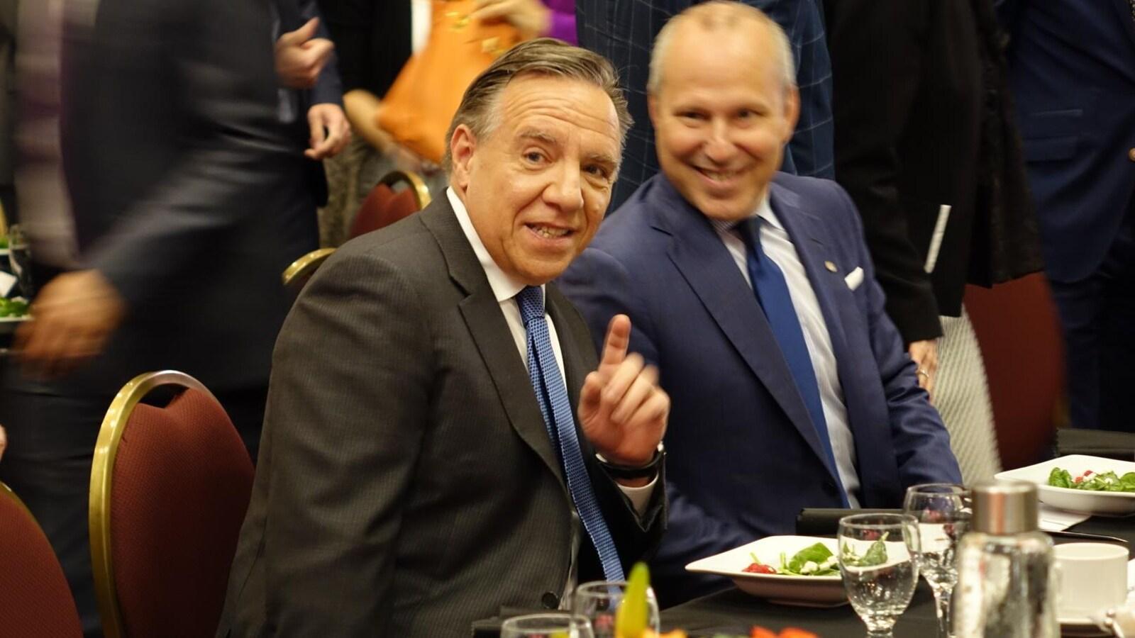 François Legault est assis à une table avec un autre convive. Devant eux sont posées des salades.